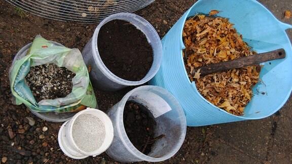 Eimer aus Kunststoff mit Kompost, Laub, Erde und weiteren Zutaten für selbstgemacht Lauberde