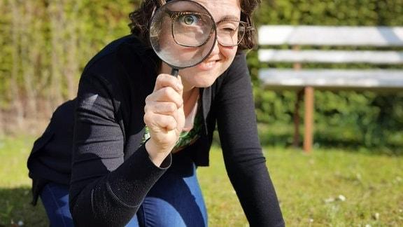 Radiomoderatorin Nadine Witt mit Lupe auf Rasen