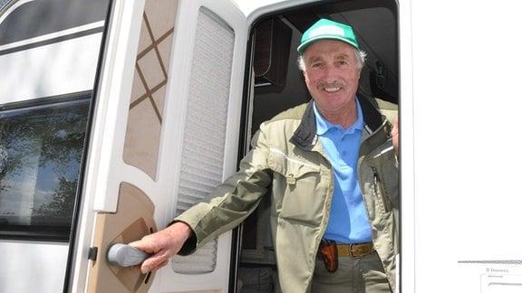 Jürgen Meister im Camper: Ein Mann in Gartenkleidung und mit Basecap öffnet die Tür eines Campers und schaut heraus. Er lächelt.