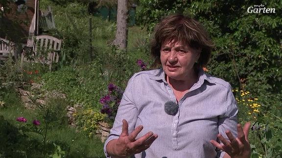 eine Frau steht im Garten und erzählt