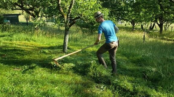 Ein Mann recht abgesenstes Gras zusammen