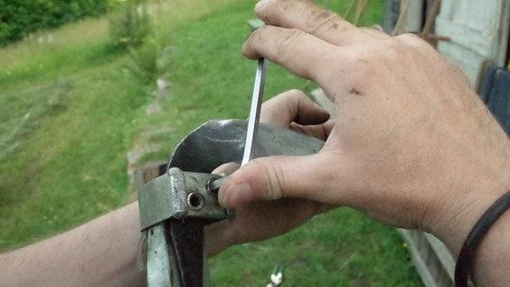 Ein Sensenblatt wird an einem Sensenbaum befestigt.