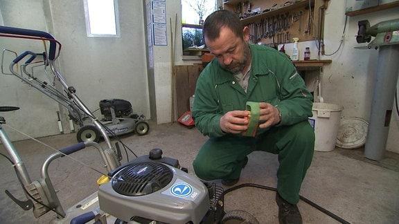 Mann arbeitet an einem Rasenmäher