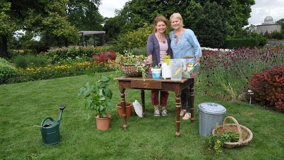 Zwei Frauen stehen im Freien hinter einem Tisch. Auf und neben dem Tisch stehen Pflanzen, Behälter und andere Materialien. Eine Gießkanne steht im Bildvordergrund.