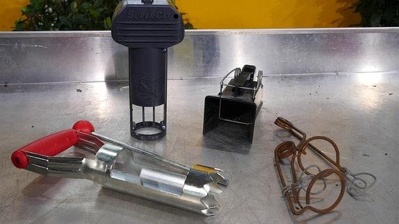 Auf einem silbernen Metalltisch liegen und stehen vier verschiedenen Mausefallen in unterschiedlichen Größen und Formen. Sie sind aus Metall und Plastik.
