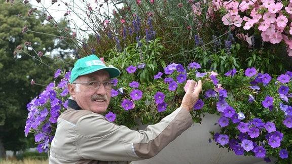 Gärtner Jürgen Meister steht vor einem üppig blühenden riesigen Blumenkübel.