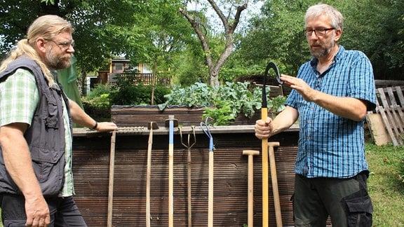 Jörg Heiß und Gartenexperte Martin Krumbein beratschlagen über das Gartenwerkzeug Sauzahn