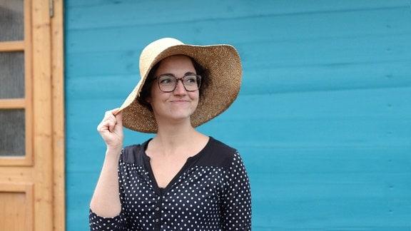 Radiomoderatorin Nadine Witt steht vor einer türkisen Bretterwand.