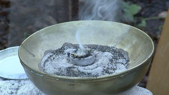 In einer Metallschale werden Kräuter geräuchert