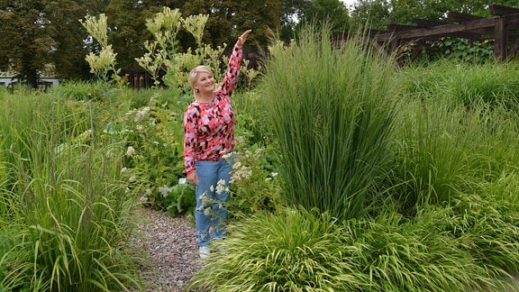Moderatorin Diana Fritzsche Grimmig steht neben einem Gras, das sie überragt.