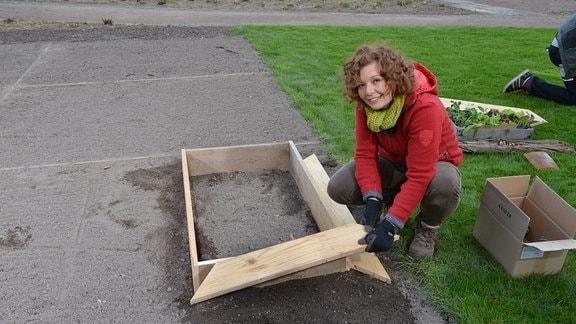 Eine Frau hockt auf einem Beet und baut eine Schneckenbarriere – einen Rahmen aus Holz.
