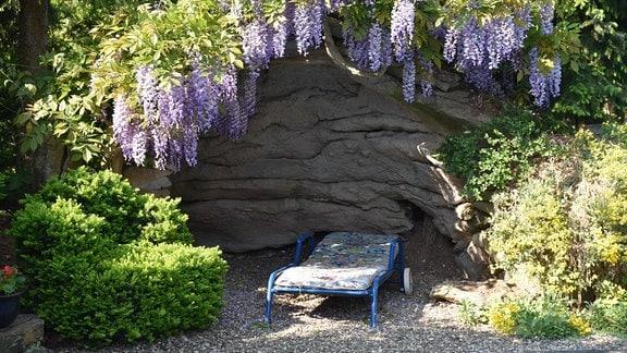 Aus Beton hergestellte, halb überdachte Sitzecke mit Liegestuhl in einem Garten