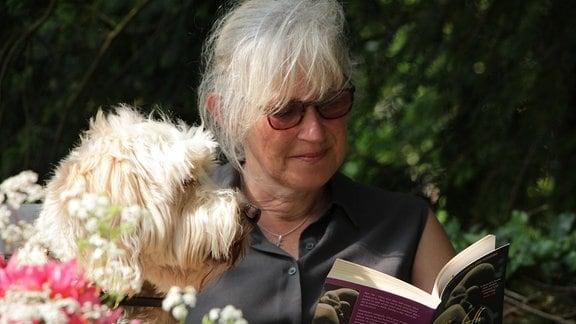 Gartenjournalistin Victorica Summerley liest mit ihrem Hund Rufus ein Buch.