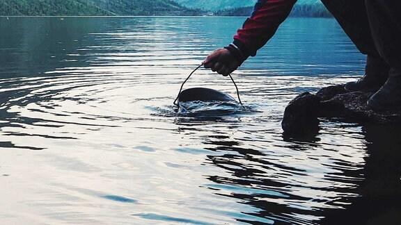 Ein Eimer wird in Wasser getaucht.