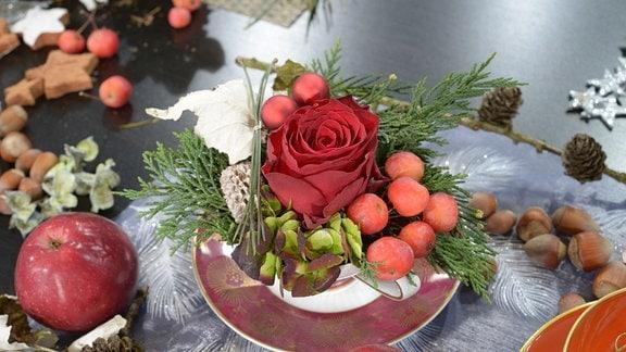 In einer Sammeltasse steckt eine Rose und Weihnachtsdekoration.