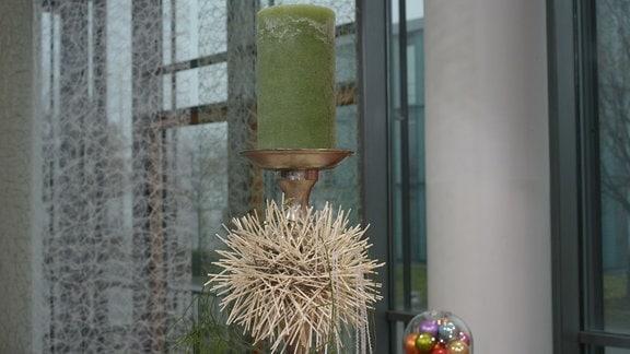 An einem Kerzenständer ist ein Ball aus dünnen Hölzstäben befestigt.