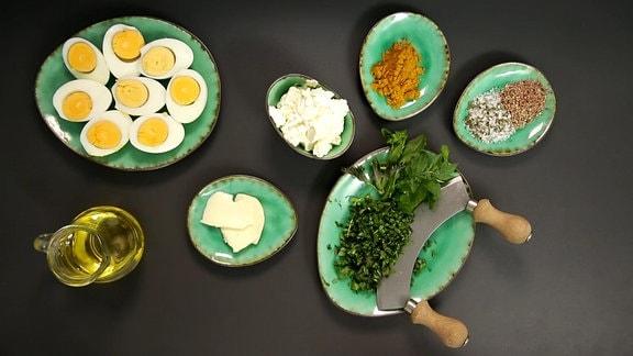 Auf einem Tisch liegen Teller mit verschiednenen Zutaten für Wildkräuterei: Eier, gewürze, kräuter, Kräuterhobel, Öl