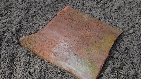 Auf einem Beet liegt ein Ziegelstein