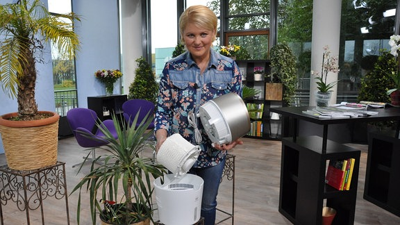 Eine blonde Frau hält Plasteteile eines Gerätes in den Händen.