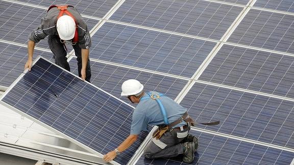 Männer installieren eine Solaranlage.