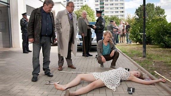 Schmücke (Jaecki Schwarz, 2. von links) und Schneider (Wolfgang Winkler, links) stehen vor der Leiche eines Mädchens.