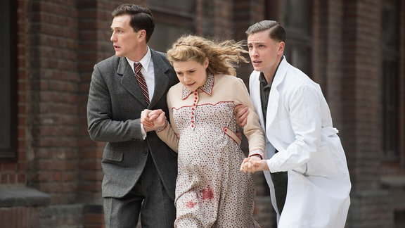 Dr. Artur Waldhausen (Artjom Gilz, l.) und Otto (Jannik Schümann, r.) bringen Anni (Mala Emde, M.) in die Charité. Bei Anni haben die Wehen eingesetzt, sie verliert massiv Blut.