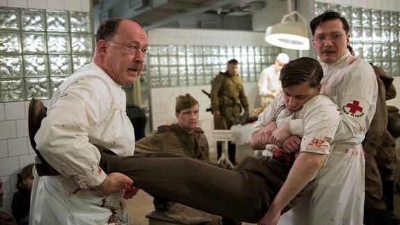 Prof. Sauerbruch (Ulrich Noethen, l.) und Martin Gruber (Jacob Matschenz, r.) kümmern sich um den schwerverletzten Otto Marquardt (Jannik Schümann, M.).
