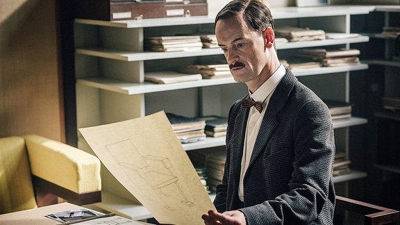 Walter Gropius (Jörg Hartmann) geht in seinem Büro Lottes Bewerbung am Bauhaus durch.