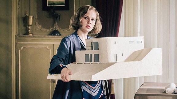 Lotte (Alicia von Rittberg) präsentiert dem Ehepaar Ludwig das fertiggestelle Modell ihrer geplanten Villa.