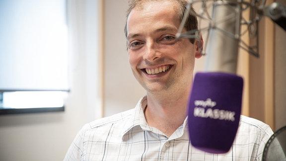 Porträt von Alexander Schmitt, lächelnd mit hellem Hemd, im MDR KLASSIK-Studio, im Vordergrund unscharf ein MDR KLASSIK-Mikrofon