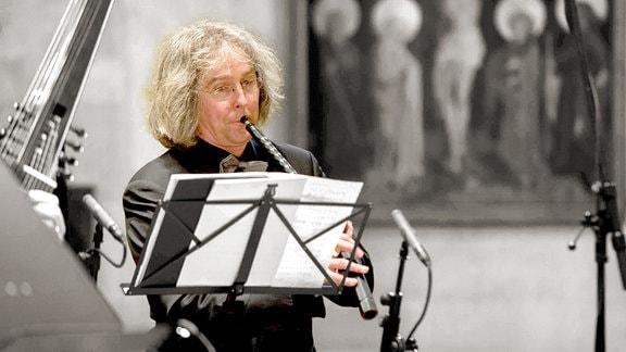Arno Paduch (in Farbe) steht mit Instrument vor Notenständer, Vordergrund und Hintergrund (schwarzweiß) zeigen Fragmente von Ensemble