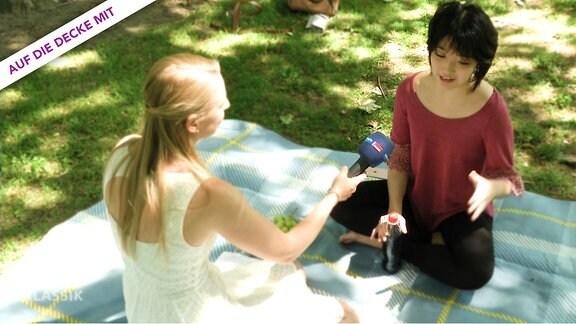 """MDR-Klassik-Redakteurin und Interviewpartnerin auf einer Picknickdecke, oben links Schriftzug """"Auf die Decke mit"""""""