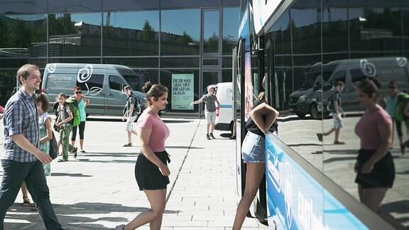 Alexander Schmidt und zwei Mädchen steigen in den Bus zum Kinderchor-Chorlager