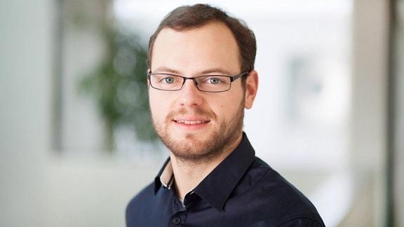 Porträt von Christof Weiss, junger Mann mit Brille, leicht lächelnd