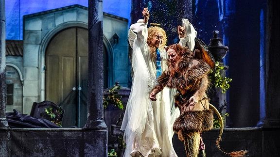 """Szene aus der Iszenierung von """"Der Teufel auf Erden"""" mit einem Teufel in klassischer Darstellung und neben ihm, größer als er, ein Engel – von links: Matthias Winter ( als Rupert), Alexander Kuchinka (als Ruprecht)"""