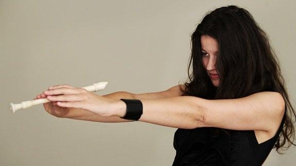 Junge Frau mit dunklen, schulterlangen Haaren blickt eine Blockflöte an, die sie mit beiden Händen auf sich ziehlend festhält