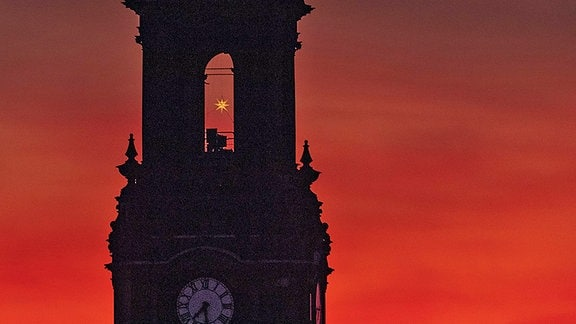 Morgenrot hinter der Dreikönigskirche in Dresden (Ausschnitte zwischen Uhr und Spitze), im Turmfenster ein Herrnhuter Stern der gelb leuchtet