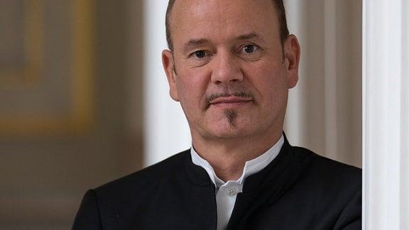 Porträt von Mann mit kurzen, dunklen Haaren, kleinem Oberlippen- und Kinnbart, verschränkte Arme und Anzug, freundlich-neutraler Blick in Kamera, unscharfer Räumlichkeit im Hintergrund