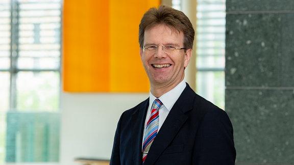 Gerlad Mertens, Geschäftsführer der Deuschen Orchestervereinigung – Lachender Mann an Betonsäule in Büro