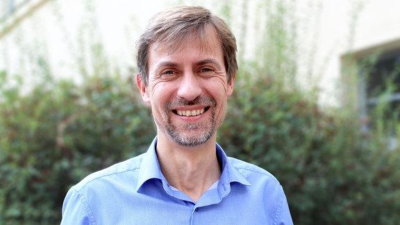 Porträt von Gregor Nowak, Geschäftsführer des Schuhmannhauses in Leipzig – Mann mit Bart lächelnd vor unscharfem Hintergrund