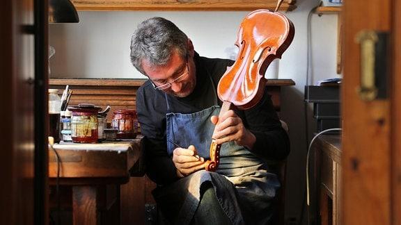 Geigenbaumeister Ekkard Seidl lackiert eine Geige in seiner Werkstatt in Markneukirchen (Sachsen).