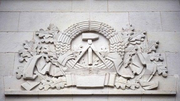 Staatliches Symbol der DDR mit Hammer und Zirkel an der Leipziger Oper