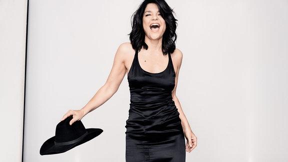 Frau mit schulterlangen schwarzen Haaren, schwarzem langen Kleid und schwarzem Hut in der Hand läuft lachend auf die Kamera zu