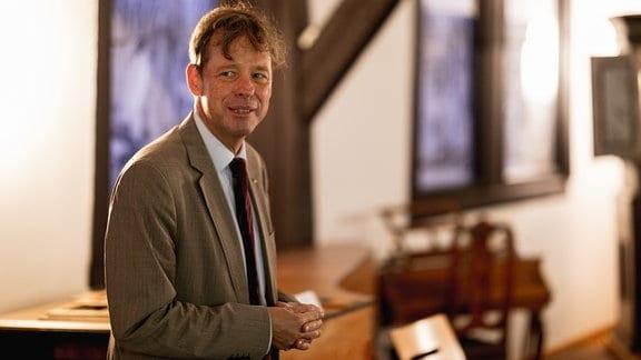 Halbnahe Aufnahme von Jörg Hansen (zur Seite blickend, Hände zusammen, vor unscharfem Hintergrund), dem Leiter des Bachhaus Eisenach