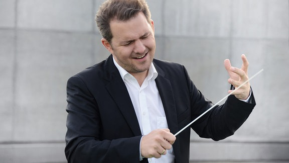 Mann mit schwarzem Sakko und weißem Hemd und Taktstock, Dirigentengeste mit der linken Hand, konzentriert-fröhlichen nach unten blickend