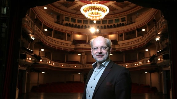Generalintendant Kay Kuntze im Theatersaal des Landestheaters Altenburg, dunkle, festliche Stimmung, Kronleuchter und Ränge im Hintergrund, im Vordergrund Porträt des Intendanten