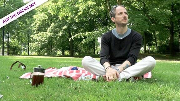Ein Mann Mitte Dreißig sitzt auf einer Picknick-Decke im Schillerpark Leipzig, vor ihm eine French-Press-Kaffeekanne