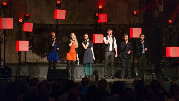 Drei junge Frauen und drei junge Männer stehen auf einer Bühne und singen in ein Mikrofon. Im Vordergrund dunkel Zuschauer, Hintergrund dunkel. Rot-beleuchtete Würfel mit den Buchstaben für acapella hängen herunter.