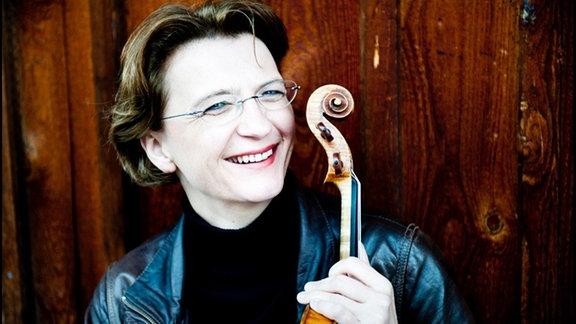 Frau mit Geige lacht in die Kamera