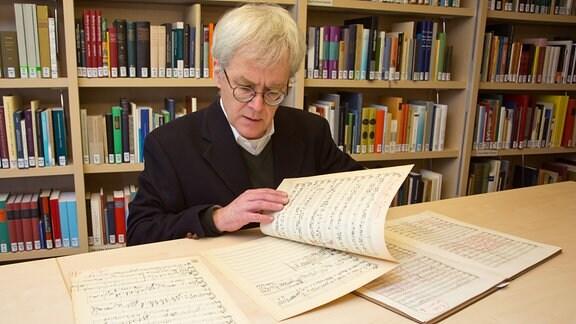 """Mann in Anzug und mit Brille sitzt vor einer Bücherwand. Er blättert in Notenblättern. Zitattafel: """"Bach-Gesamtausgabe aus Gustav Mahlers Nachlass im Besitz des Bach-Archivs."""""""